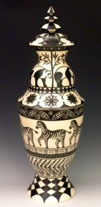 A black and white ceramic vessel with nature scenes