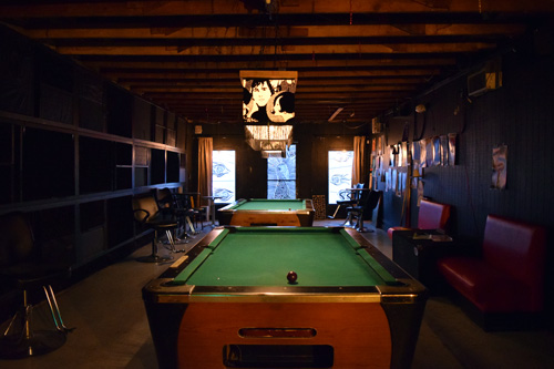 Inside view of Dozen Street Bar with pool tables and mosaic door