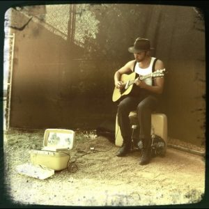 Shakey Graves Playing Guitar on Suitcase