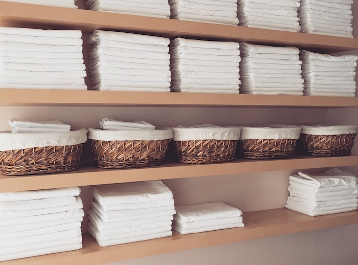 Shelves of white towels at Mantis Massage in Austin