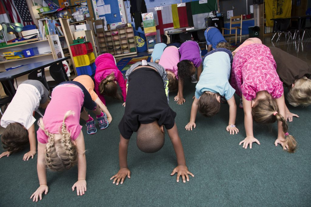 Pre-k students practicing mindful stretching