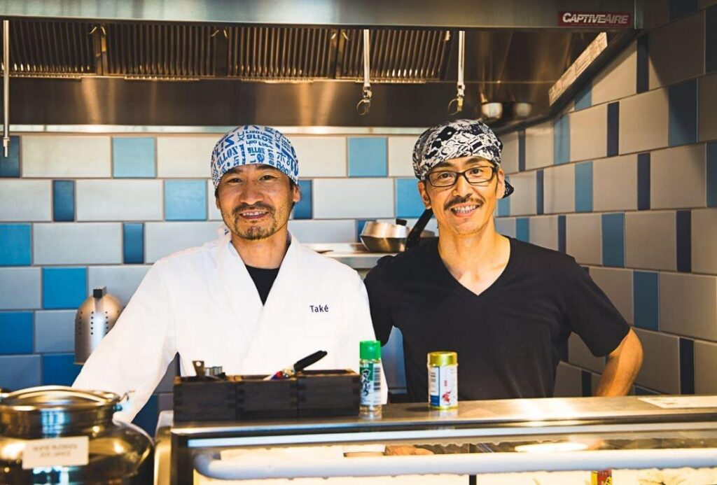 Two sushi chefs standing in a clean shiny restaurant kitchen