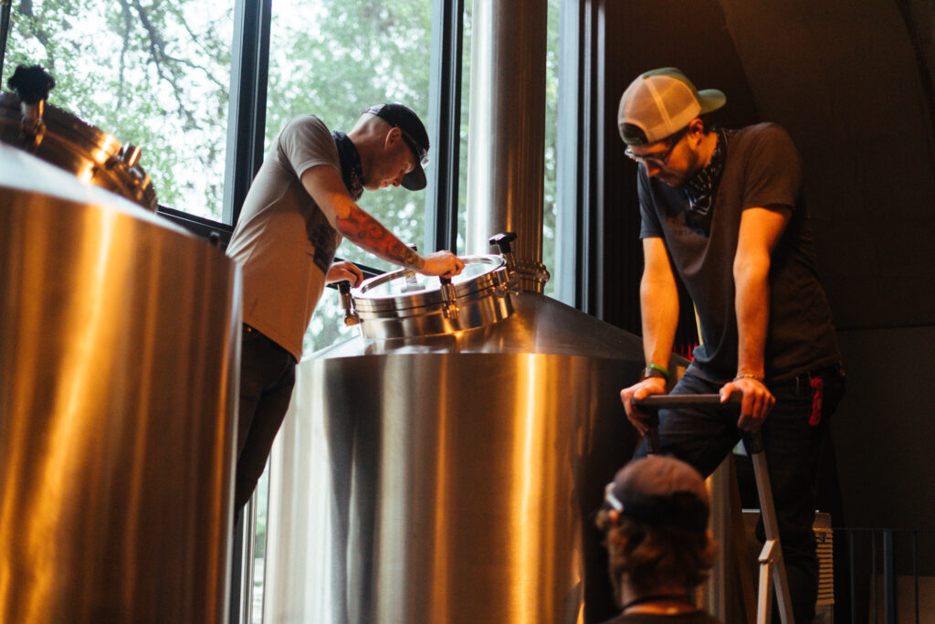Brewers inspecting brewing vessel