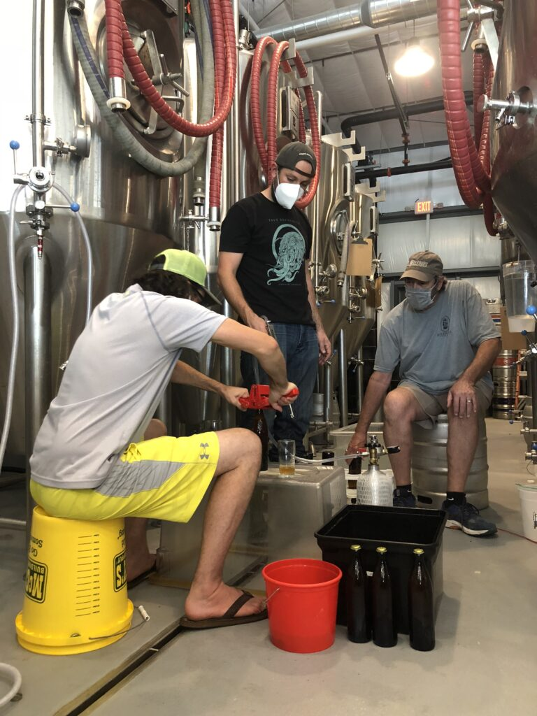 three guys wearing masks and standing or sitting next to big silver beer tanks and bottling beer
