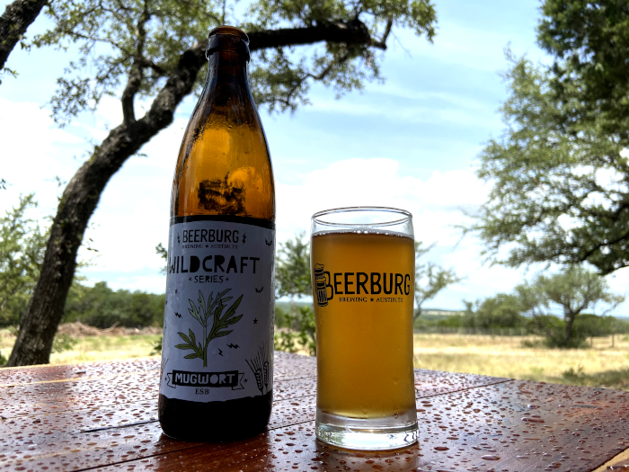 bottle of wildcraft beer next to a full glass of beer branded with Beerburg, sitting on a table wet from rain with trees and a field in the background