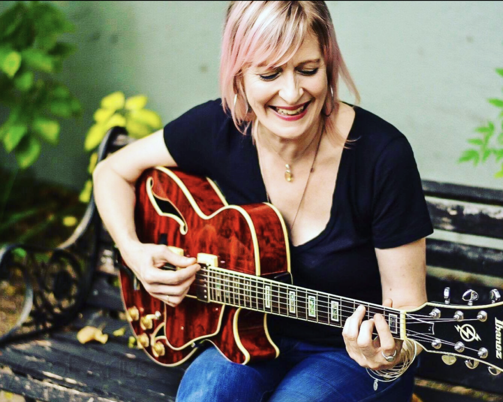 a smiling woman with light pink hair is sitting on a bench playing a beautiful wooden guitar, looking down at her hands