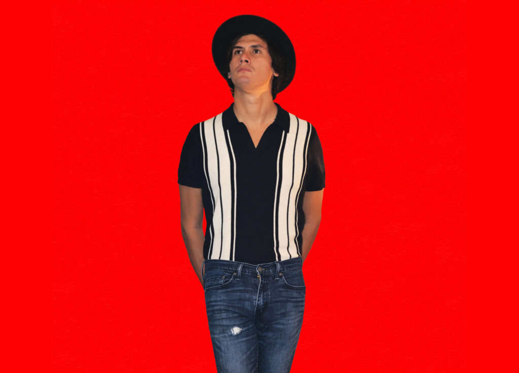 a tall man in a black hat and a vertically striped shirt with jeans is standing against a brightly colored wall and looking up at the sky