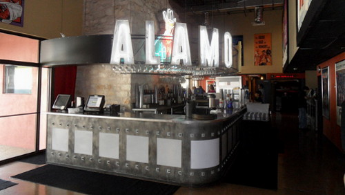 Alamo Drafthouses have bars in the lobbies to make the wait easier.