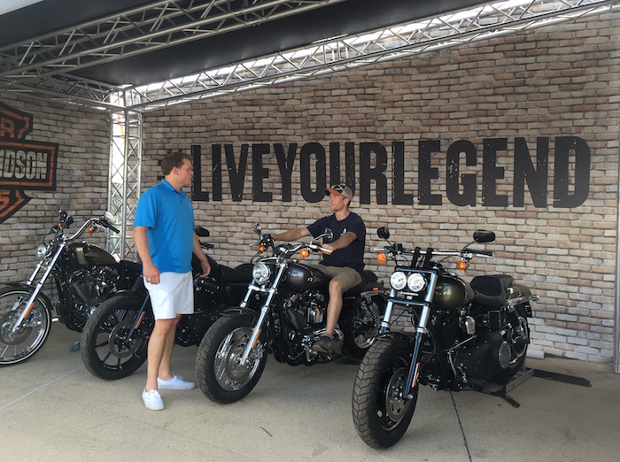 Two men at X Games Austin try out a Harley-Davidson at the sponsor's Galleria booth