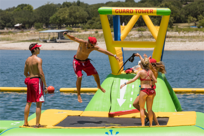 Waterloo Adventures lifeguards playing on floating obstacle course