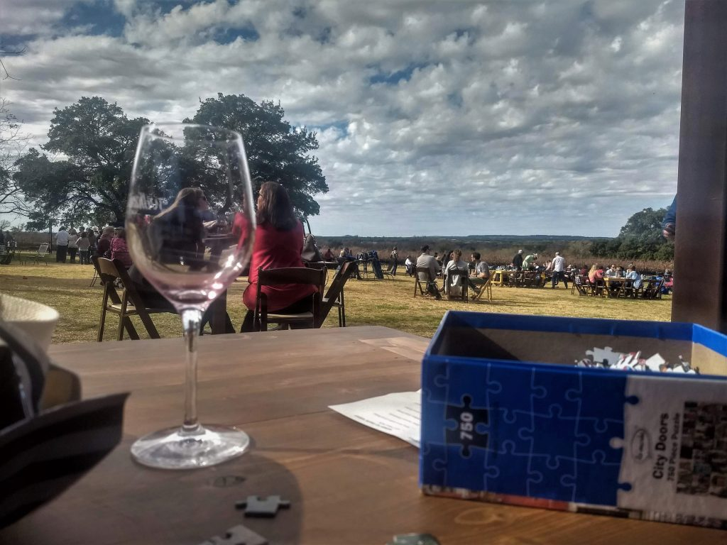Puzzle and wine on a table overlooking William Chris Vineyards